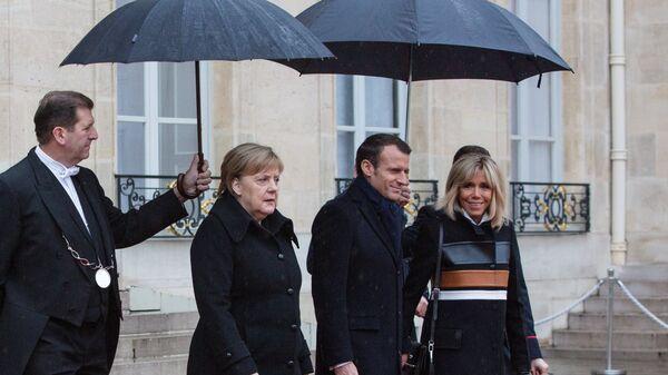 Канцлер ФРГ Ангела Меркель, президент Франции Эммануэль Макрон и его супруга Бриджит выходят из Елисейского дворца перед началом мероприятий, посвященных 100-летию окончания Первой мировой войны. 11 ноября 2018