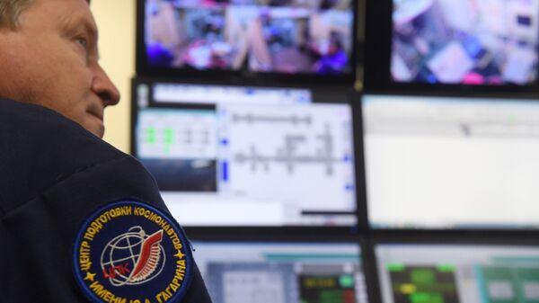 Сотрудник Центра подготовки космонавтов за пультом управления
