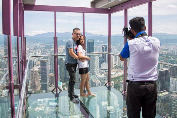 Фотограф фотографирует туристов на фоне города на смотровой площадке телебашни Менара Куала-Лумпур