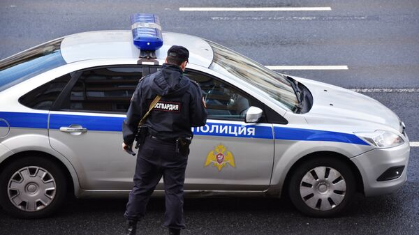 Сотрудник Росгвардии у полицейской машины