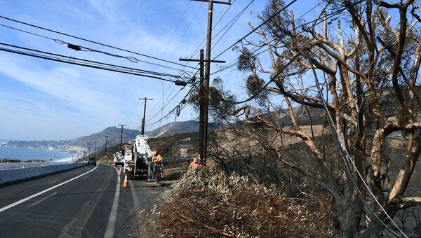 Ремонт линий электропередачи, поврежденных в результате лесных пожаров, в окрестностях города Малибу в штате Калифорния