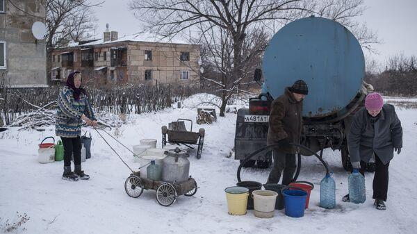 Местные жители набирают воду из цистерны в поселке Донецкий Луганской области