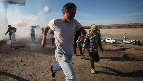 Мигранты бегут от слезоточивого газа, распыленного американскими пограничниками. 26.11.2018