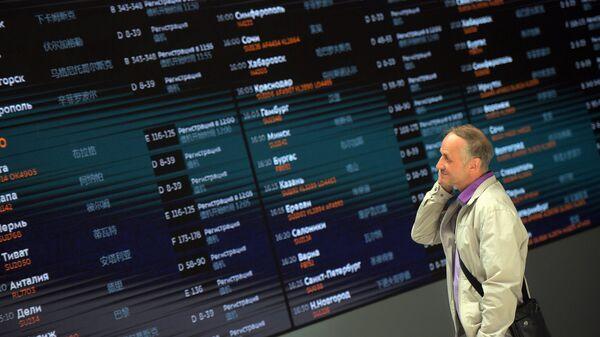Пассажир у табло  в терминале B международного аэропорта Шереметьево