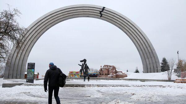 Изображение трещины, наклеенное неизвестными активистами из-за конфликта между Россией и Украиной, на Арке дружбы народов в Киеве