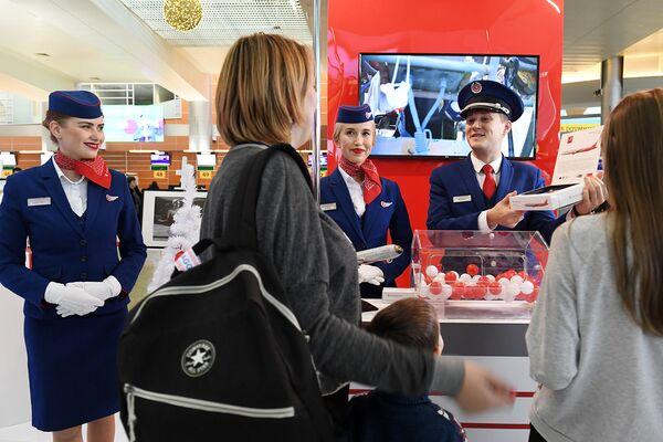 Бортпроводники авиакомпании «Россия» разыгрывают призы среди пассажиров во время акции Я делаю добро в России в терминале D аэропорта Шереметьево в Национальный день добровольца