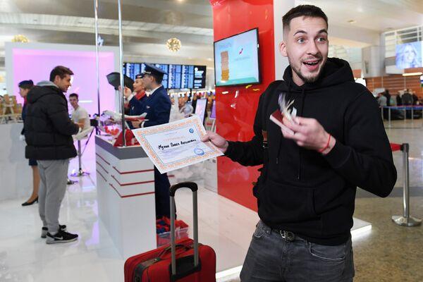 Пассажир с призом лотереи, проходящей во время акции Я делаю добро в России в терминале D аэропорта Шереметьево в Национальный день добровольца