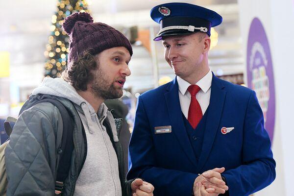 Бортпроводник авиакомпании «Россия» общается с пассажиром во время акции Я делаю добро в России в терминале D аэропорта Шереметьево в Национальный день добровольца