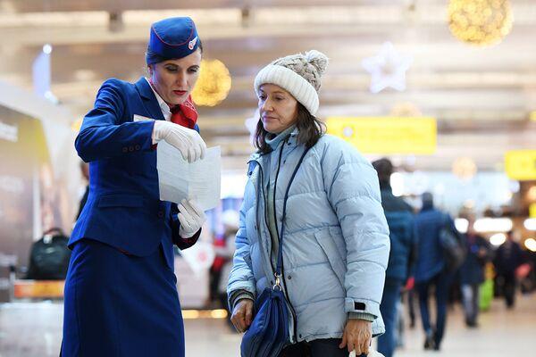 Бортпроводница авиакомпании «Россия» общается с пассажиром во время акции Я делаю добро в России в терминале D аэропорта Шереметьево в Национальный день добровольца
