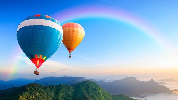 Воздушные шары, летящие над горой