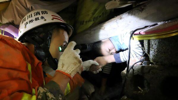 Пожарный помогает мальчику, застрявшему в обломках после оползня в провинции Сычуань, Китай. 9 декабря 2018