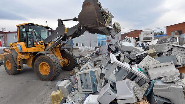 Рабочий собирает электронную и радио аппаратуру для последующей переработки
