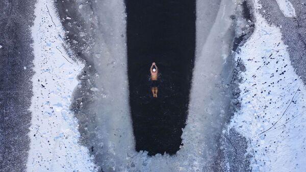 Человек плавает в частично замерзшем озере в Шэньяне, провинция Ляонин