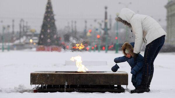 Женщина с ребенком смотрят на Вечный огонь на Марсовом поле в Санкт-Петербурге
