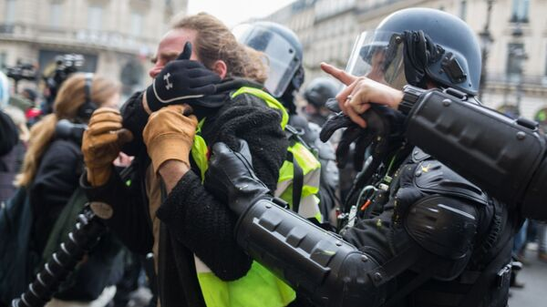 Сотрудники полиции задерживают участника акции протеста движения автомобилистов желтые жилеты в Париже.