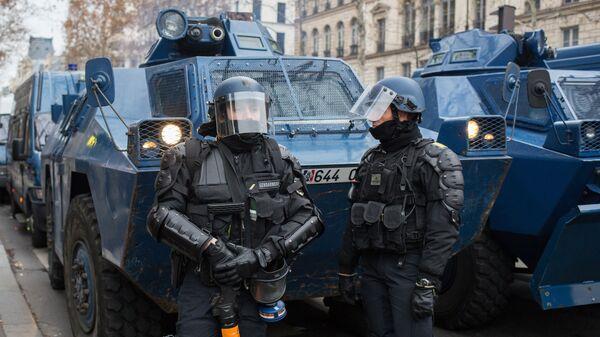 Сотрудники полиции у бронетранспортеров во время акции протеста желтые жилеты Париже. 16 декабря 2018