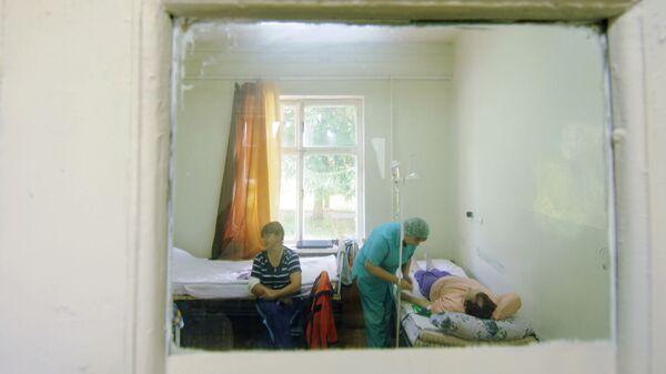 Медсестра Шимской центральной районной больницы ставит пациенту капельницу