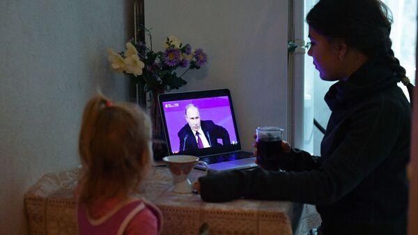 Женщина с ребенком в Симферополе смотрит прямую трансляцию ежегодной большой пресс-конференции президента РФ Владимира Путина