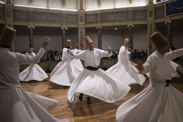Дервиши выступают на церемонии, посвященной годовщине смерти Джалаладдина Руми в Стамбуле