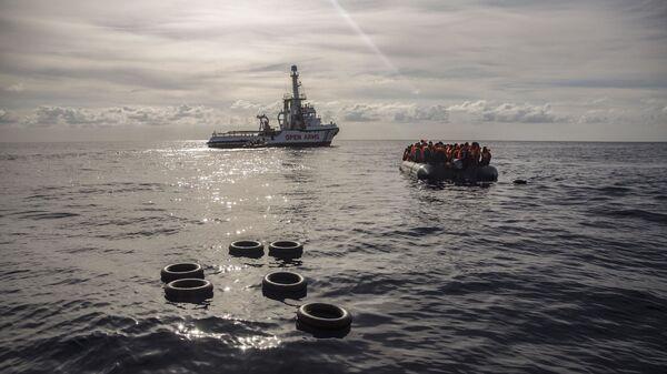 Лодка со спасенными мигрантами направляется к судну Open Arms в Средиземном море. 21 декабря 2018