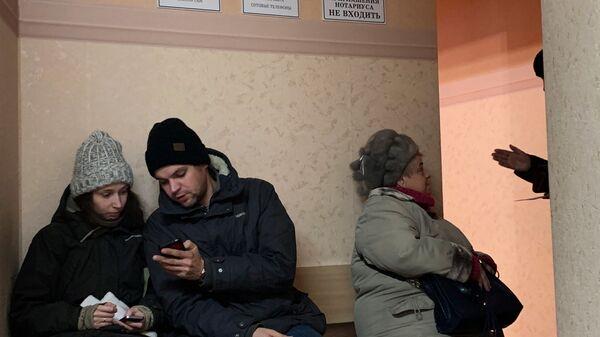 Люди сидят в очереди к нотариусу