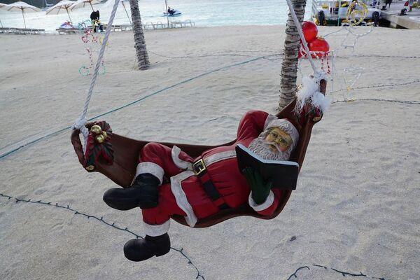 Фигура Санта Клауса в гамаке на пляже острова Сен-Мартен