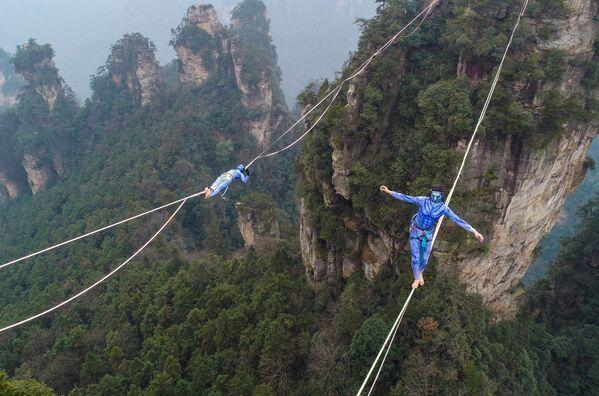 Два участника, одетые как персонажи из фильма «Аватар», во время соревнования по слэклайну в горах Хуаншичжай в центральной китайской провинции Хунань