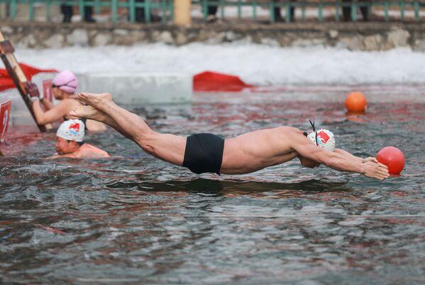 Мужчина во время зимних соревнований по плаванию при температуре минус 21 градуса Цельсия в Шэньяне, провинция Ляонин на северо-востоке Китая