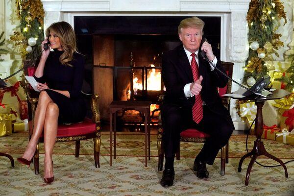 Президент США Дональд Трамп и первая леди Меланья Трамп во время рождественской горячей линии