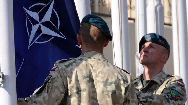 Военнослужащие поднимают флаг НАТО на базе в Афганистане. Архивное фото