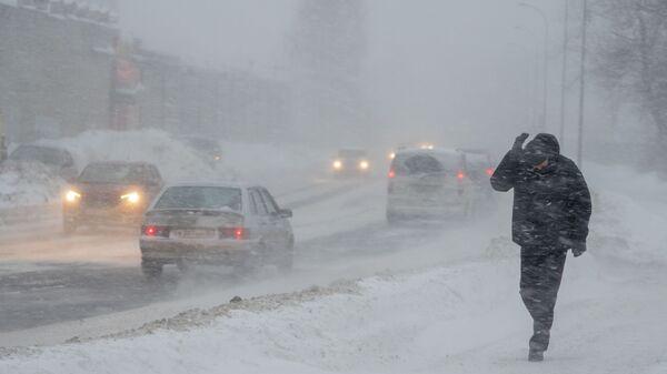 Прохожий на одной из улиц в Петрозаводске во время снегопада