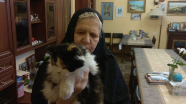 Сестра Серафима с кошкой на территории Богородице-Рождественского женского монастыря в селе Барятино, Калужская область