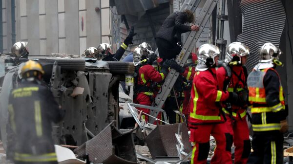 Пожарные эвакуируют женщину с места взрыва в пекарне в 9-м округе Парижа, Франция. 12 января 2019