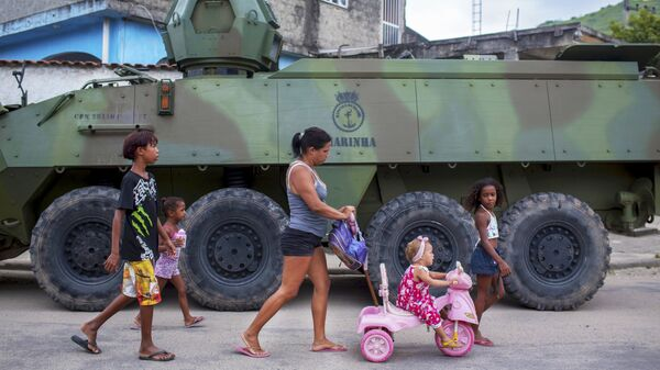 Семья проходит мимо бронетранспортера во время спецоперации в Рио-де-Жанейро, Бразилия