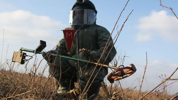 Сапер инженерных войск ЮВО в защитном костюме во время разминирования местности в в Чеченской Республике