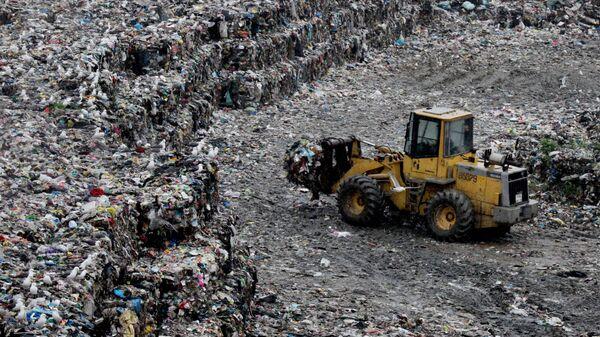 Трактор работает на полигоне для складирования твердых бытовых отходов