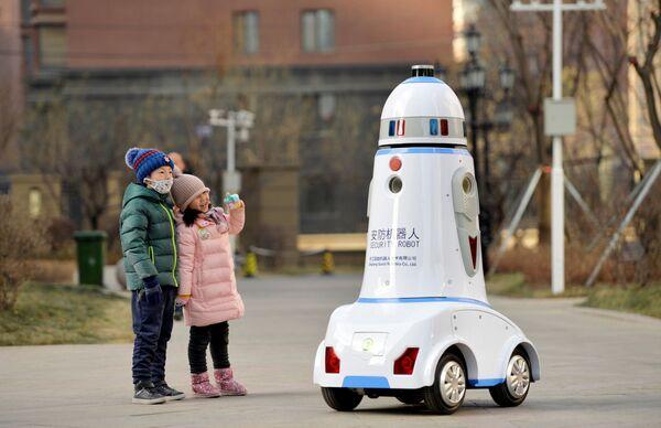 Дети стоят рядом с роботом, патрулирующим жилой квартал а в Хух-Хото, Внутренняя Монголия, Китай