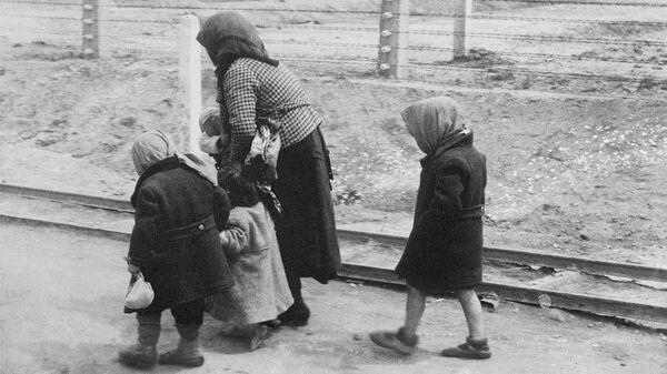 Еврейка из Венгрии с детьми идут в газовые камеры Освенцима, май или июнь 1944 года