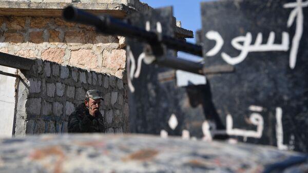 Сирийский ополченец на позициях напротив Джебхат-ан-Нусры (запрещенная в РФ террористическая группировка) в пригороде Алеппо