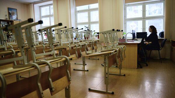 Преподаватель в пустом учебном классе школы