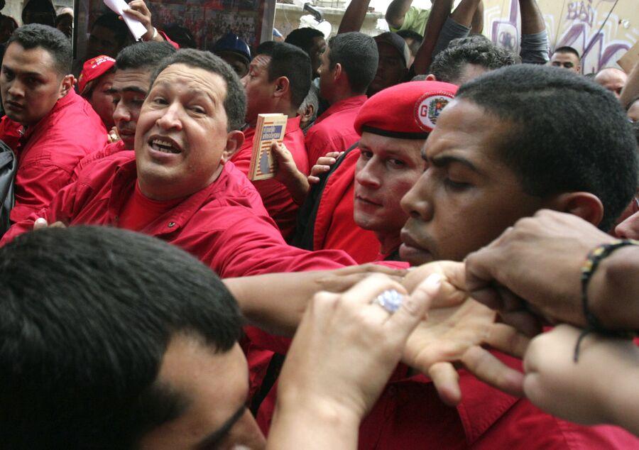 Президент Венесуэлы Уго Чавес приветствует сторонников во время визита в бедный район Каракаса