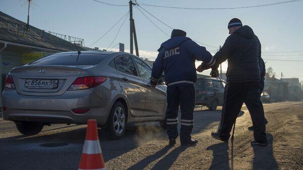 Сотрудник дорожно-патрульной службы ГИБДД на месте дорожно-транспортного происшествия
