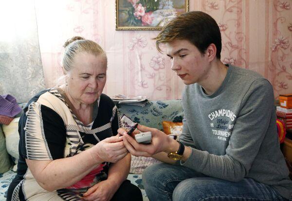 Волонтер помогает подключить приставку для цифрового эфирного телевидения жительнице города Гаврилов Ям
