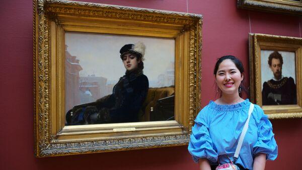 Девушка у картины Незнакомка русского художника Ивана Крамского в Третьяковской галерее в Москве