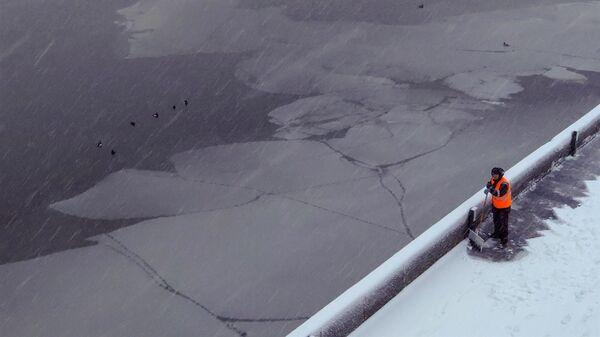Сотрудник коммунальных служб убирает снег в Москве