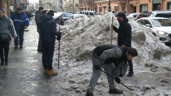 Бармены расчищают снег и наледь на улице Рубинштейна в Санкт-Петербурге