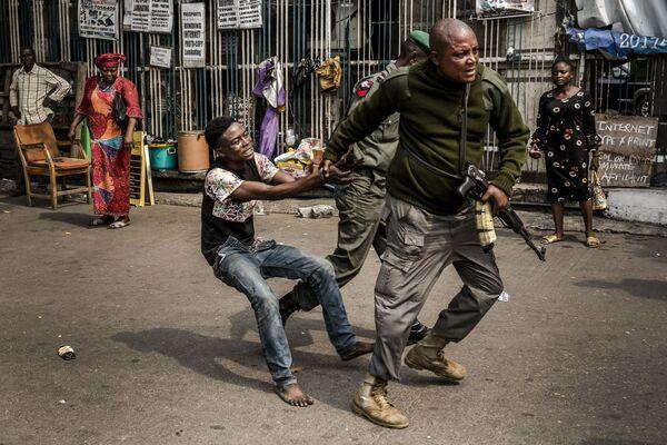 Сотрудник полиции задерживает вора на площади Tafawa Balewa в Лагосе, Нигерия