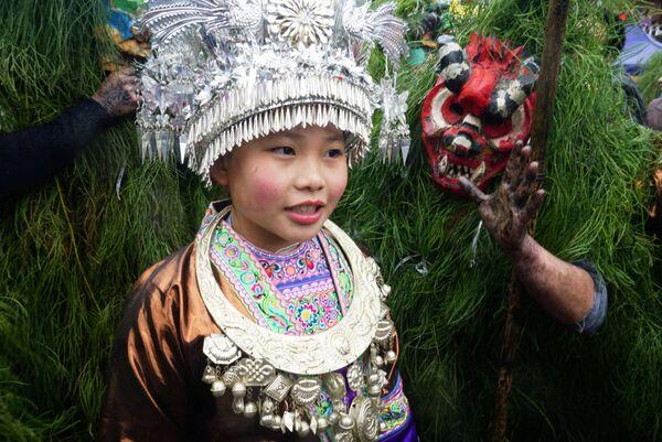 Девочка в национальном костюме народности Мяо на фестивале Мангхао в Китае