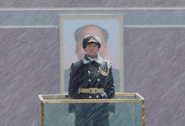 Военный стоит в карауле у портрета Мао Цзэдуна во время снегопада в Пекине