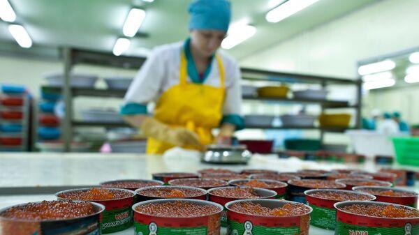 Сотрудница рыбоперерабатывающего завода Ясный взвешивает расфасованную в консервные банки икру перед закаткой